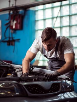 Male technician at car service station is repairing vehicle